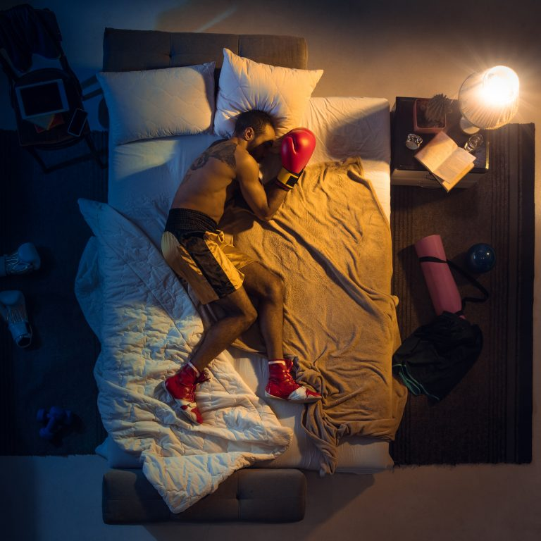 top-view-young-professional-boxer-fighter-sleeping-his-bedroom-sportwear-with-gloves-768x768-1